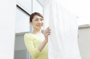 バスタオルを干す女性の写真素材 [FYI02815418]