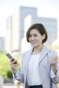 スマートフォンで音楽を聴くビジネスウーマンの写真素材 [FYI02815436]