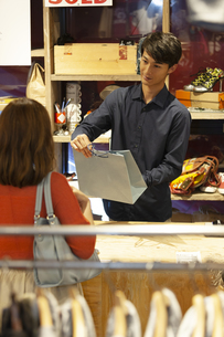 ショッピングバッグをお客に渡す店員の写真素材 [FYI02815487]