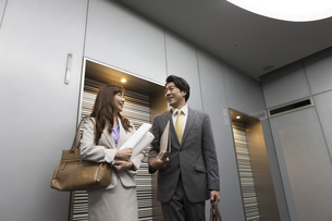 エレベーター前を歩く男女のビジネスマンの写真素材 [FYI02815504]