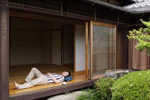 縁側で寝転ぶ男性の写真素材 [FYI02815603]