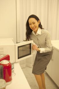 電子レンジを開ける女性の写真素材 [FYI02815619]