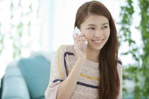 スマートフォンで話す女性の写真素材 [FYI02815671]