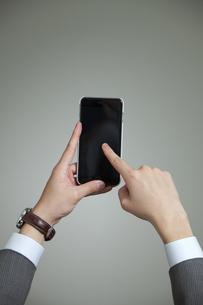 スマートフォンを操作するビジネスマンの手元の写真素材 [FYI02815680]