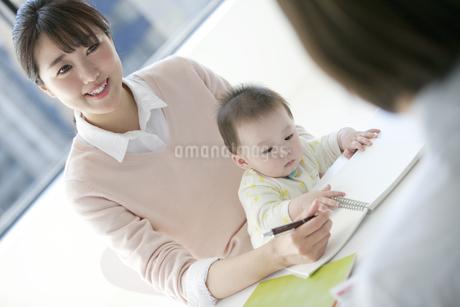 膝に座る赤ちゃんと母親の写真素材 [FYI02815695]