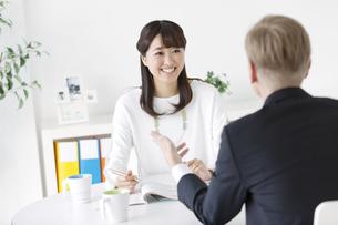 英会話を学ぶ女性と外国人講師の後姿の写真素材 [FYI02815745]