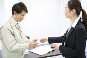 名刺を交換するビジネスマンとビジネスウーマンの写真素材 [FYI02815782]