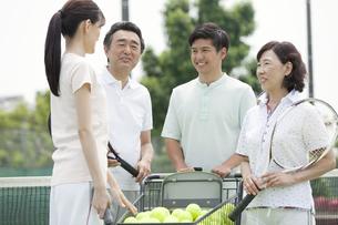テニスコートで話す男女4人の写真素材 [FYI02815864]