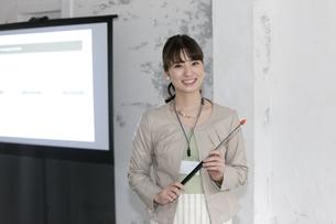 プロジェクターの前に立つビジネス女性の写真素材 [FYI02815867]