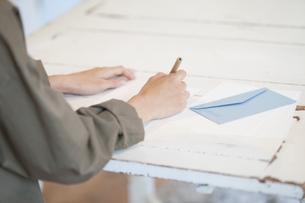 テーブルで手紙を書く女性の手元の写真素材 [FYI02815883]