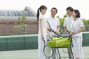 テニスコートに立つ男女4人の写真素材 [FYI02815940]