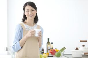カップを持ってキッチンに立つ女性の写真素材 [FYI02815960]