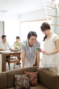 携帯電話を見る若い夫婦の写真素材 [FYI02815978]