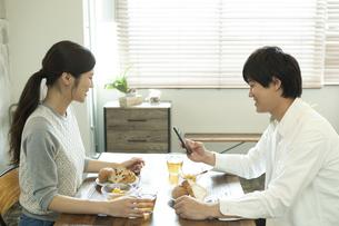 テーブルで飲食をするカップルの写真素材 [FYI02816060]