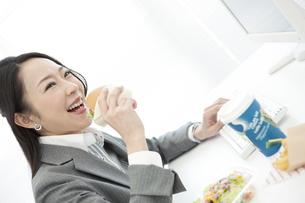 ハンバーガーを食べるビジネスウーマンの写真素材 [FYI02816102]