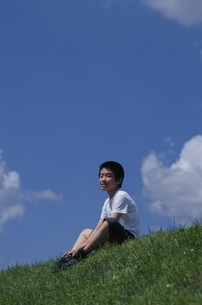 青空の下の草原に座る日本人の男の子の写真素材 [FYI02816253]
