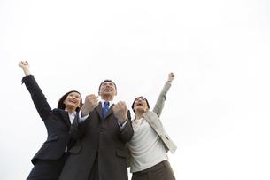 ガッツポーズをするビジネスマンとビジネスウーマン3人の写真素材 [FYI02816761]