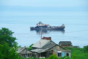 コルサコフ沖合の廃船と家の写真素材 [FYI02817339]