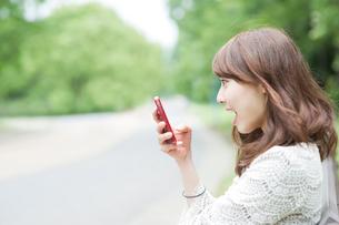 スマートフォンを見て驚く女性の写真素材 [FYI02817979]