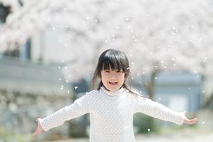 桜吹雪で遊ぶ女の子の写真素材 [FYI02818004]