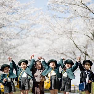 桜並木で手を上げる6人の幼稚園児の写真素材 [FYI02818018]
