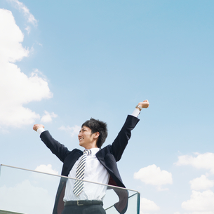 青空バックに伸びをするビジネスマンの写真素材 [FYI02818026]