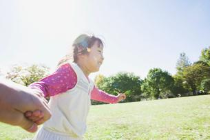 手をつないで公園を走る女の子の写真素材 [FYI02818065]