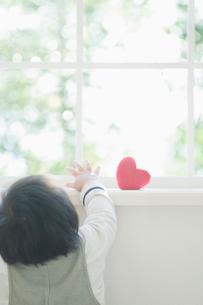 ハートのオブジェを取ろうとする赤ちゃんの写真素材 [FYI02818086]