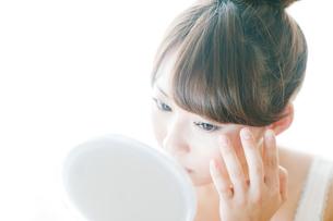 化粧をチェックする女性の写真素材 [FYI02818138]