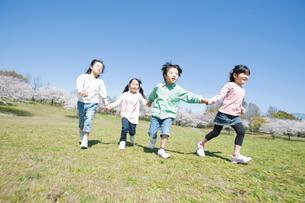 手をつないで走る4人の子供達の写真素材 [FYI02818258]