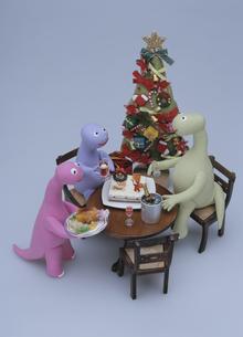 クリスマスツリーと食卓を囲む恐竜の家族の写真素材 [FYI02818273]