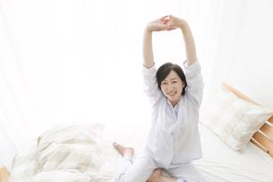 ベッドで伸びをする中高年女性の写真素材 [FYI02818857]