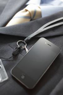 ビジネススーツの上に置かれた黒いスマートフォンとストラップの写真素材 [FYI02821507]