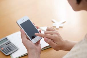 携帯電話を持って検索する女性の手と電卓の写真素材 [FYI02821522]