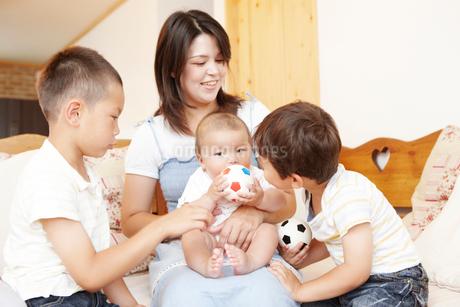 ソファの上で赤ちゃんをあやすお兄ちゃんとお母さんの写真素材 ...