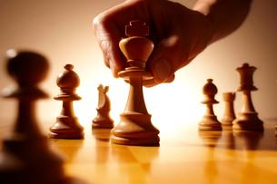 チェスのボードにキングのチェスの駒を置く手の写真素材 [FYI02822358]