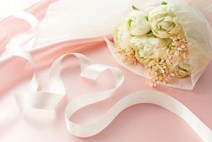 ピンクの布のドレープとブーケの花とハート型のリボンの写真素材 [FYI02822644]