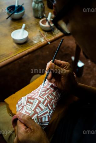 素焼きの陶器に絵付けする陶芸家の手の写真素材 [FYI02823072]
