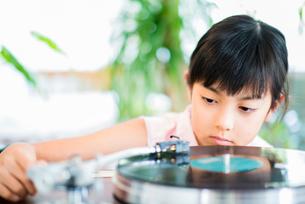 レコードプレーヤーで音楽をかける女の子の写真素材 [FYI02823075]