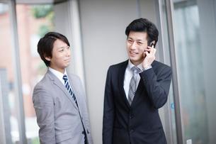 電話をするビジネスマンと同僚の写真素材 [FYI02823162]