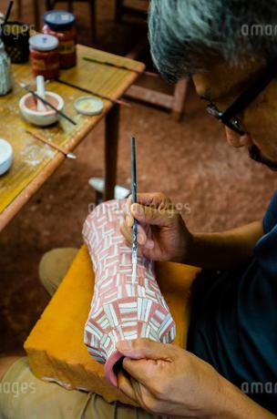 素焼きの陶器に絵付けする陶芸家の手の写真素材 [FYI02823192]