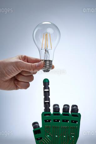電球とロボットの手の写真素材 [FYI02823683]