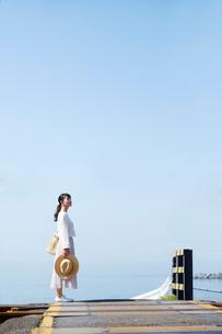 踏切で立ち止まって景色を見渡す女性の写真素材 [FYI02823705]