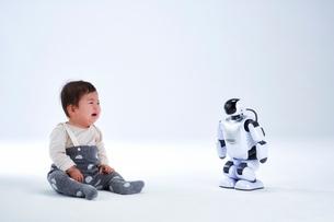 赤ちゃんと向き合うロボットの写真素材 [FYI02823732]