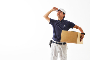白バックの空間に立つ荷物を持った作業着の男性の写真素材 [FYI02823749]