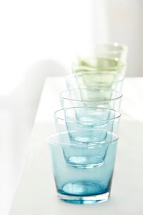 白い棚の上に並べられたブルーとグリーンのガラスのコップの写真素材 [FYI02823762]