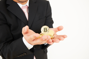 ビットコインを持ったスーツを着た男性の写真素材 [FYI02823787]