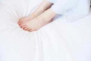 ベッドの上に座る女性の素足の写真素材 [FYI02823845]