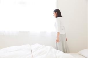 ベッドサイドをを歩く女性の写真素材 [FYI02823857]