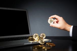 ビットコインとパソコンとコインを持つスーツを着た男性の写真素材 [FYI02823868]